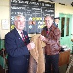 Museum President, John Brook M.B.E., accepts the sheep skin Irvin jacket from Don Hood.
